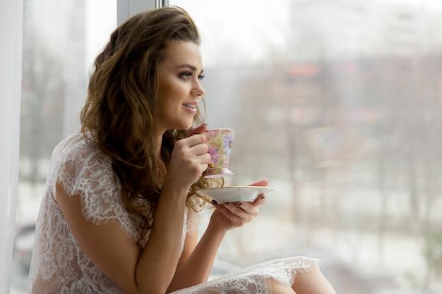 Mulher jovem sexy em lingerie erótica transparente bebe café no peitoril da janela. paisagem urbana em segundo plano.