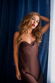Mulher jovem sexy lingerie preta fica na janela, envolvida em uma cortina