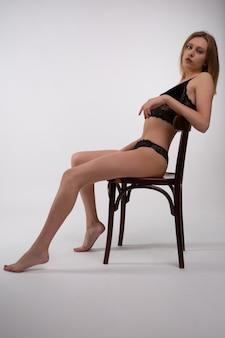 Mulher jovem sexy loira em roupa íntima de renda preta, sentada em uma cadeira de madeira