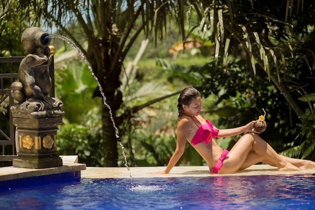 Mulher jovem sexy maiô rosa relaxante na piscina