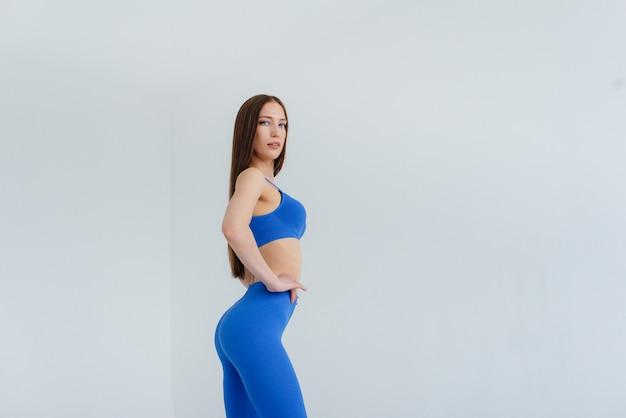Mulher jovem sexy posando com um agasalho azul. fitness, estilo de vida saudável.