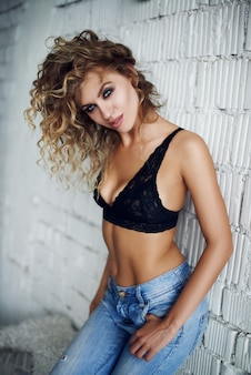 Mulher jovem sexy posando em seu quarto enquanto usava lingerie sexy
