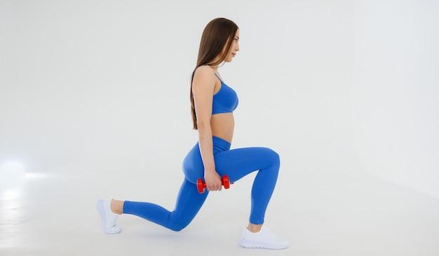 Mulher jovem sexy realiza exercícios de esportes. fitness, estilo de vida saudável.