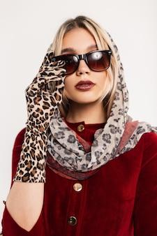 Mulher jovem sexy retrato retrô com belos lábios em um lenço de leopardo elegante na cabeça em elegantes óculos de sol em um vestido vermelho elegante em luvas da moda.