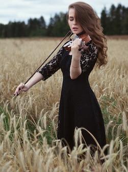 Mulher jovem sexy vestido preto entusiasticamente tocando violino em um campo de trigo com um vento forte