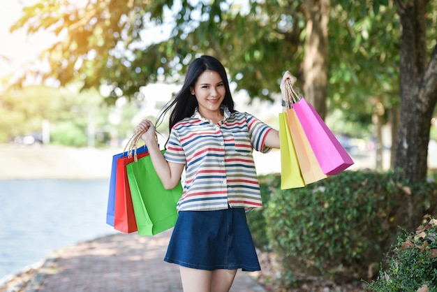 Mulher jovem, shopping, exterior, senhora, feliz, smiley, segurando, saco shopping, ao ar livre, verão