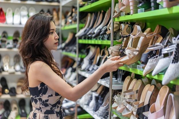 Mulher jovem, shopping, sapatos de salto alto, em, loja