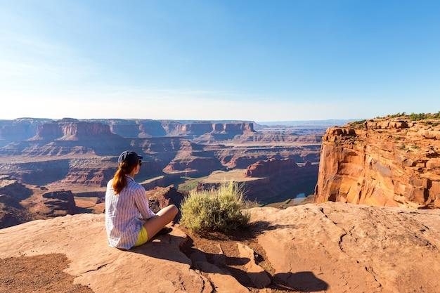 Mulher jovem situada no topo de uma montanha rochosa no vale