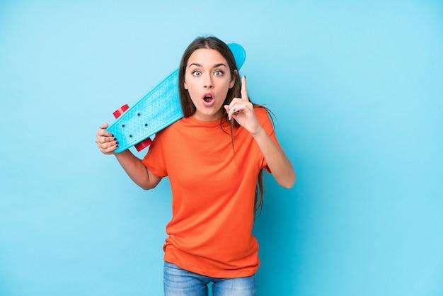 Mulher jovem skatista caucasiana isolada tendo uma ideia, o conceito de inspiração.