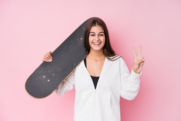 Mulher jovem skatista caucasiana segurando o skate mostrando o número dois com os dedos.