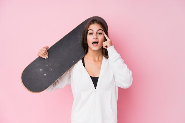 Mulher jovem skatista caucasiano segurando o skate mostrando um gesto de decepção com o dedo indicador.