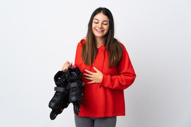 Mulher jovem skatista isolada na parede branca sorrindo muito