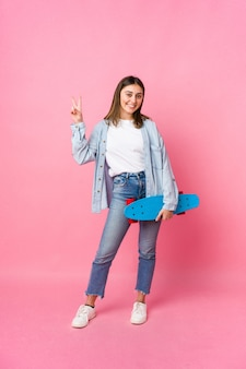 Mulher jovem skatista isolada na parede rosa