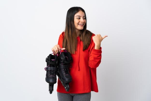 Mulher jovem skatista isolada no branco apontando para o lado para apresentar um produto