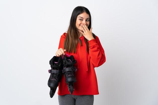 Mulher jovem skatista isolada no branco feliz e sorridente boca coning com a mão