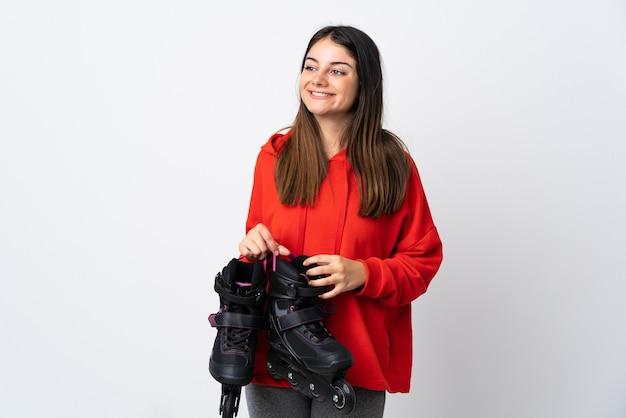 Mulher jovem skatista isolada no branco olhando para o lado e sorrindo