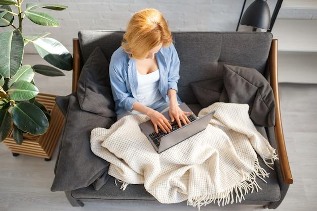 Mulher jovem sob um cobertor usando laptop no sofá