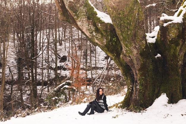 Mulher jovem sob uma enorme faia na floresta do país basco.