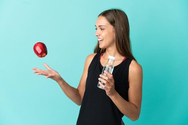 Mulher jovem sobre fundo azul isolado com uma maçã e uma garrafa de água
