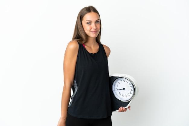 Mulher jovem sobre fundo branco isolado com balança