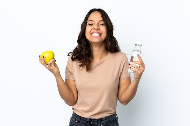 Mulher jovem sobre fundo branco isolado com uma maçã e uma garrafa de água