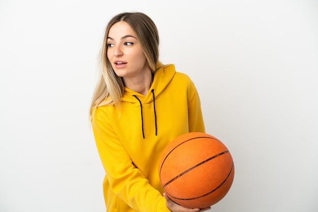 Mulher jovem sobre fundo branco isolado jogando basquete
