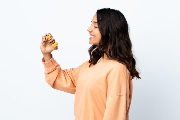 Mulher jovem sobre fundo branco isolado segurando macarons franceses coloridos e feliz