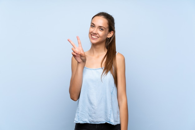 Mulher jovem, sobre, isolado, experiência azul, sorrindo, e, mostrando, sinal vitória