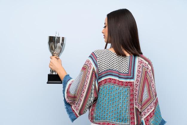 Mulher jovem, sobre, isolado, parede azul, segurando, um, troféu