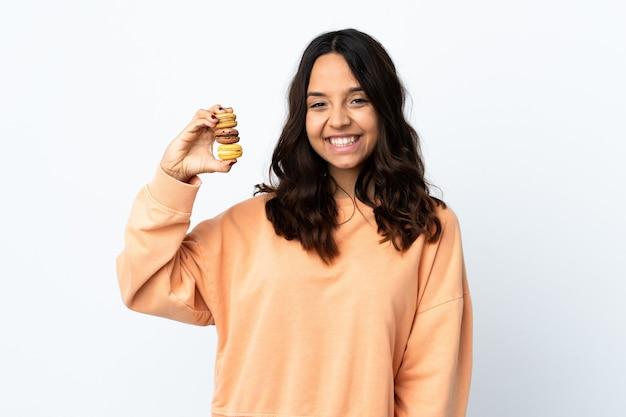 Mulher jovem sobre o branco isolado segurando macarons franceses coloridos e sorrindo muito