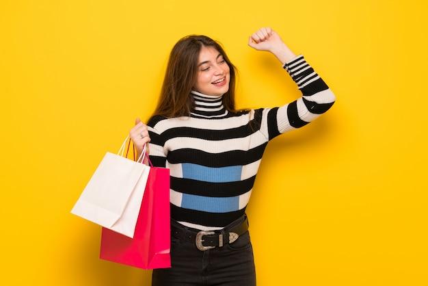 Mulher jovem, sobre, parede amarela, segurando, um, muitos, bolsas para compras, em, posição vitória