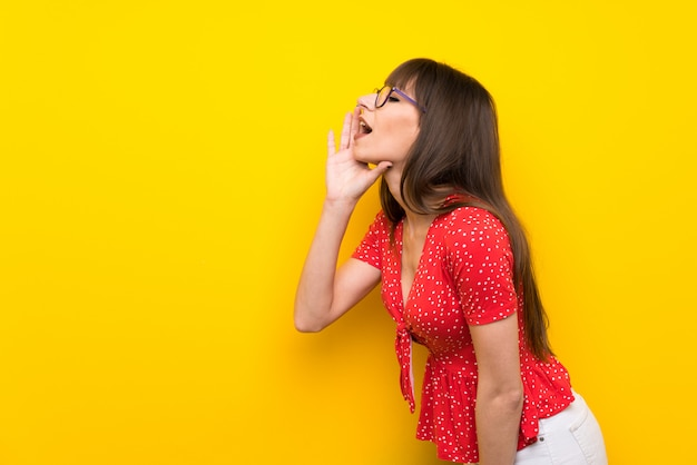 Mulher jovem, sobre, parede amarela, shouting, com, boca largo aberto, para, a, lateral