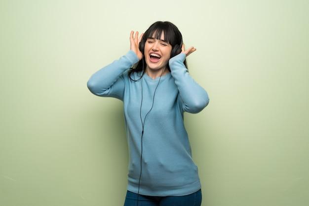 Mulher jovem, sobre, parede verde, escutar música, com, fones