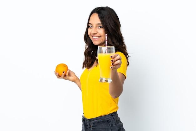 Mulher jovem sobre um branco isolado segurando uma laranja e um suco de laranja