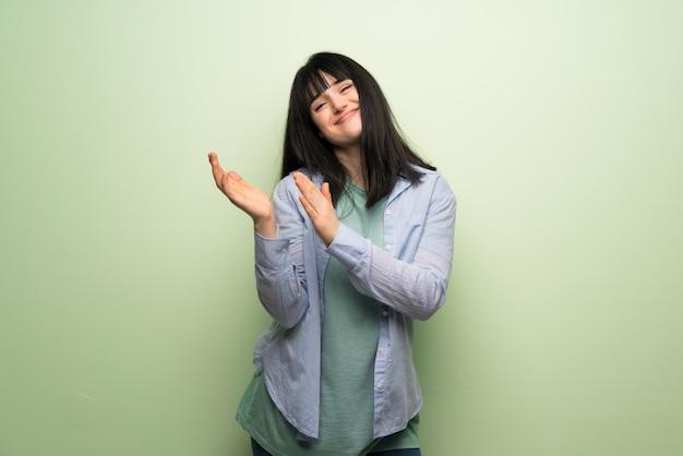 Mulher jovem, sobre, verde, parede, aplaudindo, após, apresentação, em, um, conferência