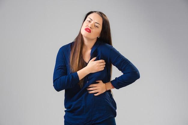 Mulher jovem sofre de dor, sente-se doente e fraqueza isolada na parede