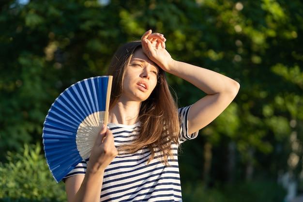 Mulher jovem sofre de insolação ao ar livre menina infeliz se sentindo mal com temperatura quente toque na testa