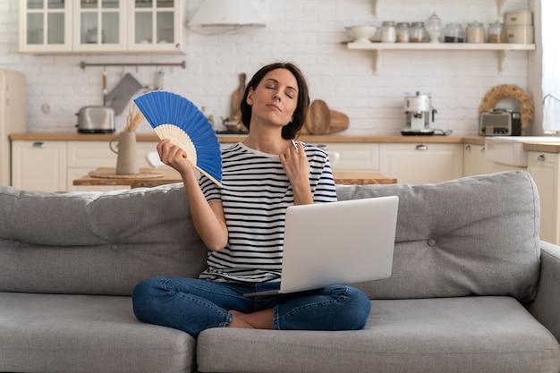 Mulher jovem sofre de insolação sem ar-condicionado acenando ventilador, sentada no sofá de casa