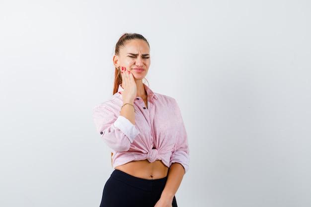 Mulher jovem sofrendo de dor de dente na camisa casual e parecendo doente. vista frontal.