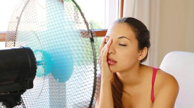 Mulher jovem sofrendo de uma onda de calor, usando um ventilador, sentada no sofá da sala de estar em casa.