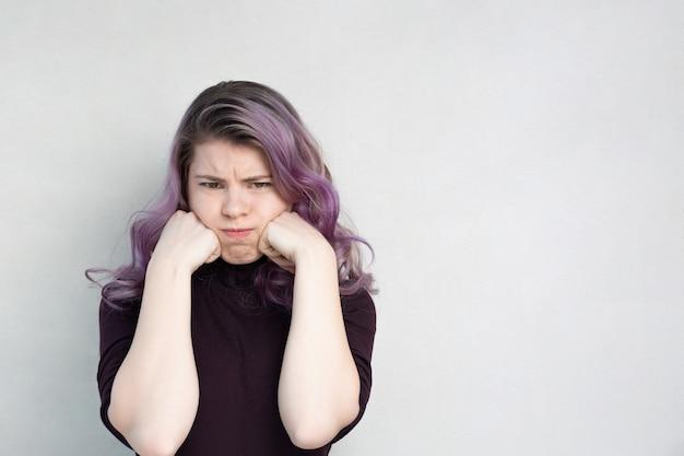 Mulher jovem solitária e chateada posando sobre um fundo cinza. espaço vazio