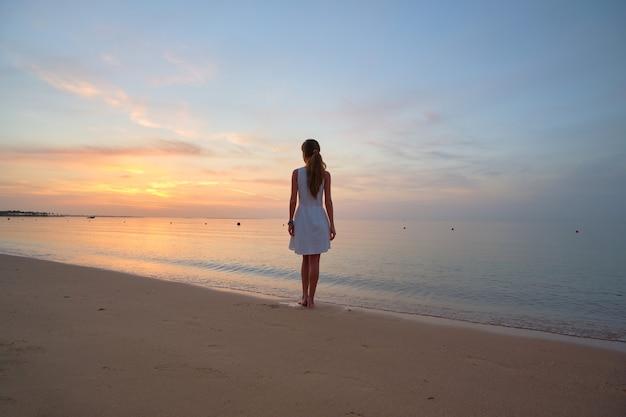 Mulher jovem solitária em pé na praia à beira-mar, desfrutando de uma noite tropical quente.