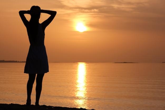 Mulher jovem solitária em pé na praia do oceano à beira-mar, desfrutando de uma noite tropical quente.