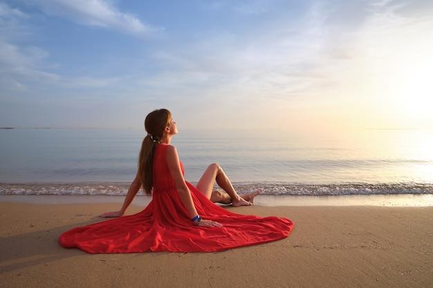Mulher jovem solitária sentada na praia de areia do oceano à beira-mar, desfrutando de uma noite tropical quente.