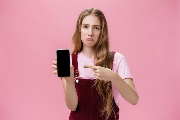 Mulher jovem sombria triste com penteado natural ondulado bonito, mostrando a tela do smartphone apontando para o gadget com o dedo indicador, fazendo cara chateada, franzindo a testa descontente, sentindo arrependimento depois de comprar o telefone quebrado.