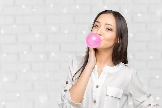 Mulher jovem, soprando, bubblegum