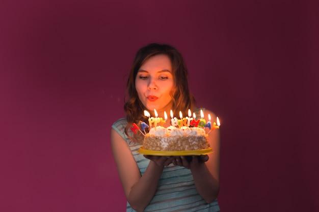Mulher jovem soprando velas em um bolo de aniversário sobre fundo vermelho.