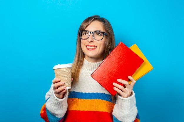 Mulher jovem sorri e segura livros e um copo de café ou chá nas mãos.