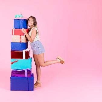 Mulher jovem sorridente, abraçando a pilha colorida de caixas de presente no pano de fundo rosa