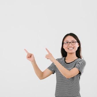 Mulher jovem sorridente apontando para cima com espaço de cópia